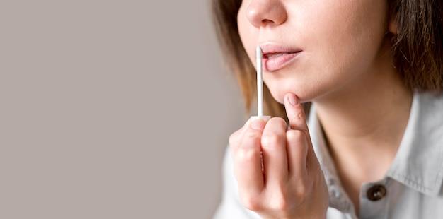 Fêmea de cópia espaço aplicando brilho labial Foto gratuita