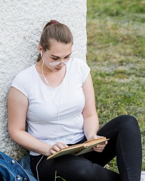 Fêmea em fones de ouvido lendo livro no gramado Foto gratuita