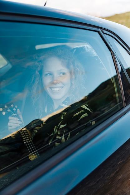Fêmea jovem alegre no carro Foto gratuita