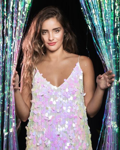Fêmea jovem bonita segurando uma cortina e usando um vestido branco Foto gratuita