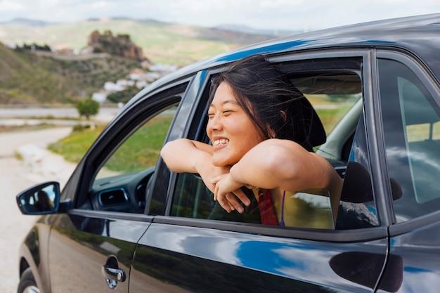 Fêmea jovem chinesa alegre olhando a natureza da janela do carro Foto gratuita