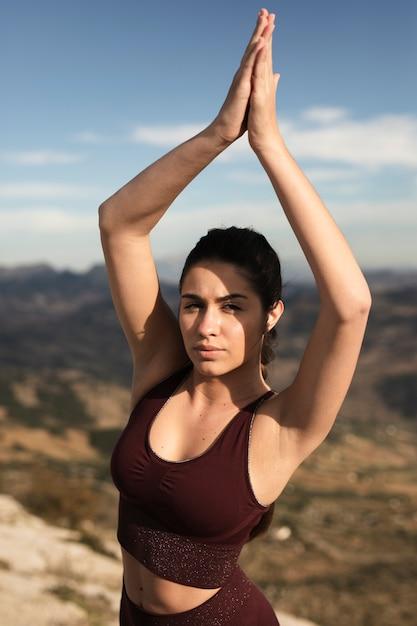 Fêmea jovem de alto ângulo na luz solar fazendo yoga Foto gratuita