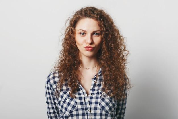 Fêmea jovem encantada com aparência atraente faz beicinho nos lábios e faz uma careta Foto gratuita
