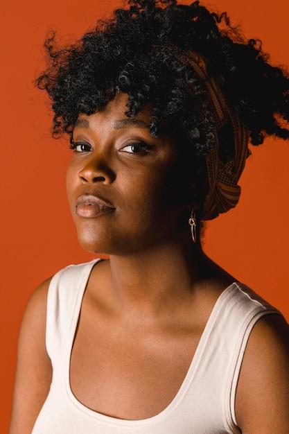 Fêmea jovem encaracolado étnica séria em t-shirt no estúdio Foto gratuita