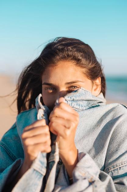 Fêmea jovem, escondendo o rosto na jaqueta jeans Foto gratuita