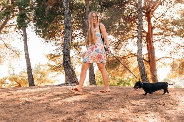 Fêmea jovem feliz passeando com seu animal de estimação no parque Foto gratuita