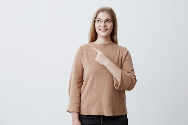 Fêmea jovem loira alegre bonita sorrindo amplamente e apontando o dedo, mostrando algo interessante e emocionante na parede do estúdio com espaço de cópia para o seu texto ou conteúdo publicitário Foto gratuita