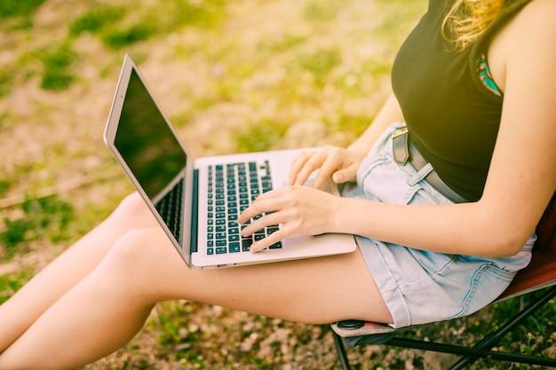 Fêmea jovem trabalhando no laptop na floresta Foto gratuita