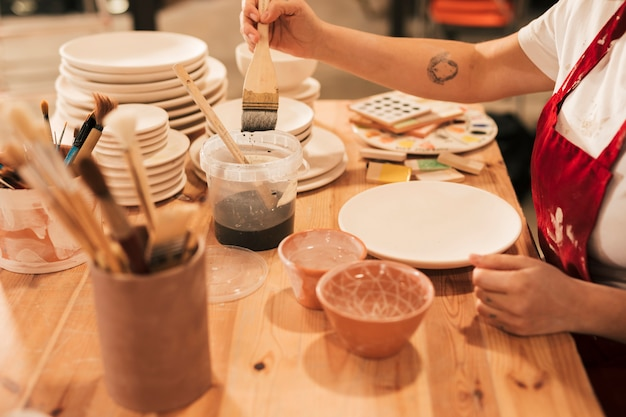 Fêmea, levando a cor cerâmica para pintar no prato com pincel Foto gratuita
