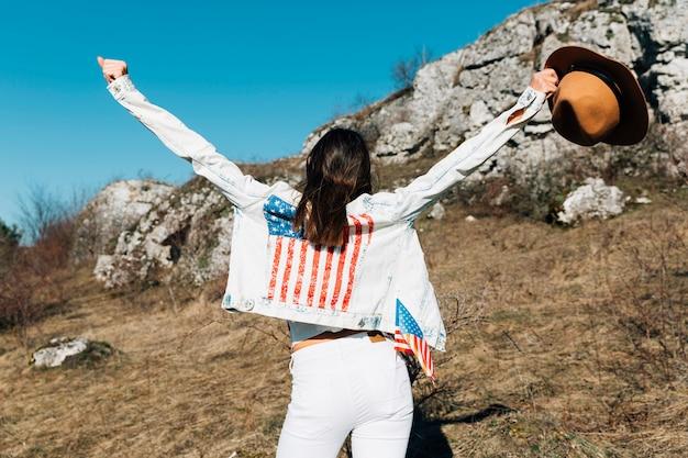Fêmea levantando as mãos com chapéu na natureza Foto gratuita