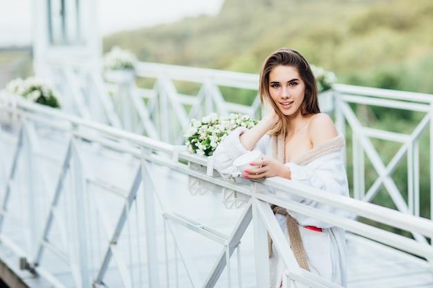 Fêmea nova de sorriso ou noiva que levanta com o copo de alguma bebida, desgastando na veste branca. Foto Premium