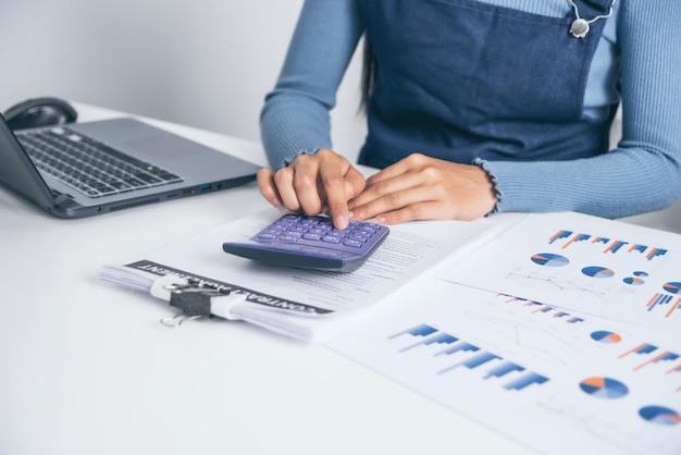 Fêmea nova do negócio que calcula o orçamento familiar, tentando economizar algum dinheiro com conta de papel financeira. Foto Premium