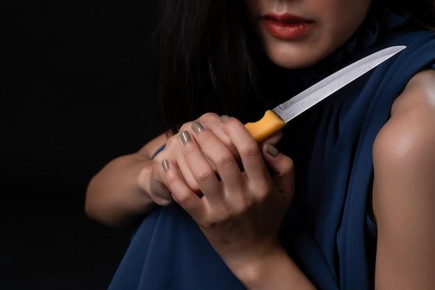 Fêmea nova triste deprimida que mantém a faca disponivel na obscuridade. Foto Premium
