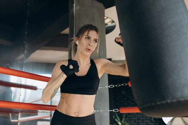 Fêmea, perfurando um saco de boxe com luvas de boxe no ginásio Foto Premium