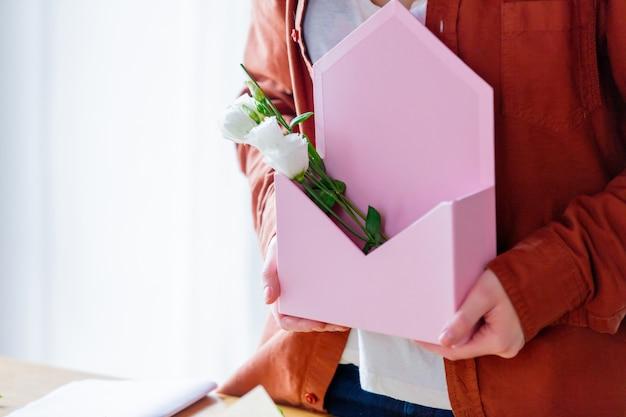 Fêmea que guarda um envelope cor-de-rosa com rosas brancas. Foto Premium