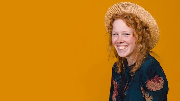 Fêmea ruiva alegre no estúdio com fundo colorido Foto gratuita