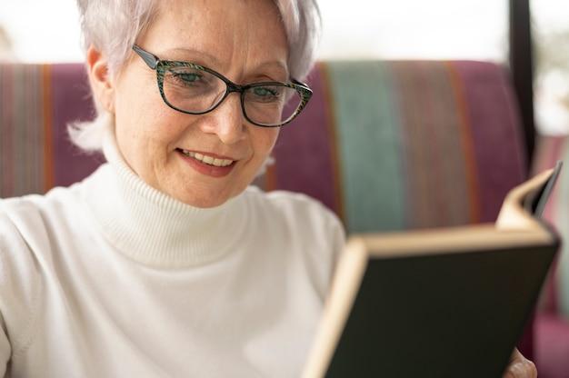 Fêmea sênior de close-up na leitura do restaurante Foto gratuita
