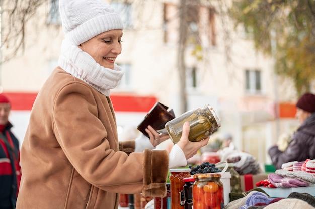 Fêmea sênior, verificando pickles frascos Foto gratuita