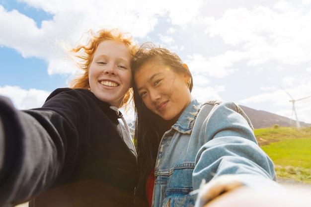 Fêmeas felizes tomando selfie ao ar livre Foto gratuita