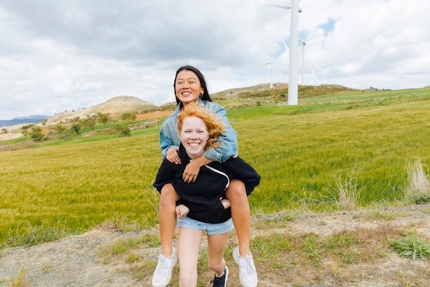 Fêmeas multiétnicas se divertindo perto de parque eólico Foto gratuita