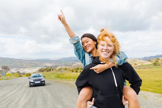 Fêmeas, tocando, piggyback, perto, estacionado, car Foto gratuita