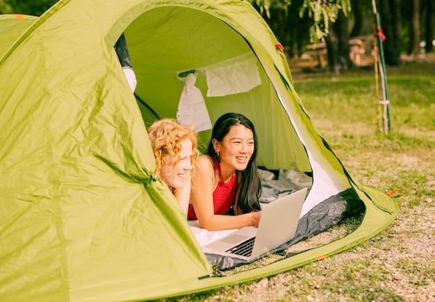 Femininas, amigos, mentindo, em, barraca, com, laptop Foto gratuita