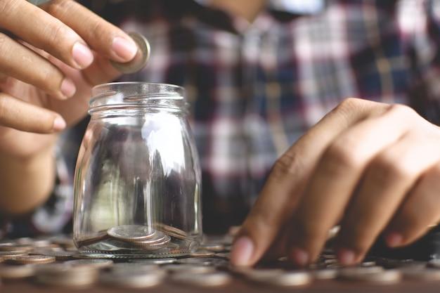 Femininas mãos largando o dinheiro em vidro jar na prancha, começar a planejar e poupar dinheiro. Foto Premium