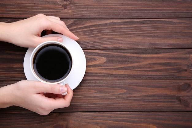 Femininas mãos segurando a xícara de café em madeira marrom. Foto Premium