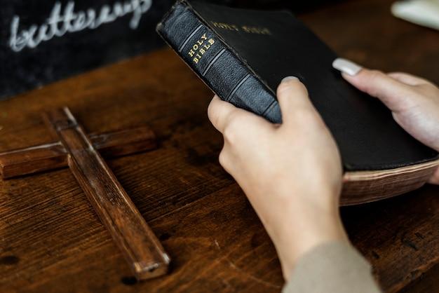 Femininas, mãos, segurando, bíblia, madeira, crucifixos Foto gratuita
