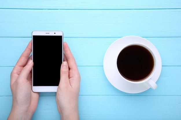 Femininas mãos segurando um smartphone e uma xícara de café sobre fundo azul de madeira. Foto Premium