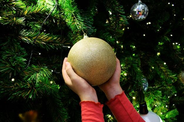 Femininas mãos segurando uma bola de ouro. árvore de natal decorada no tema prata e ouro. Foto Premium