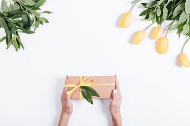 Femininas mãos segurando uma caixa de presente com fita amarela na mesa perto das tulipas Foto Premium