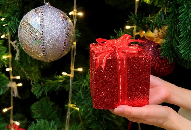 Femininas mãos segurando uma caixa de presente de glitter vermelho com ornamento de prata bola de lantejoulas Foto Premium