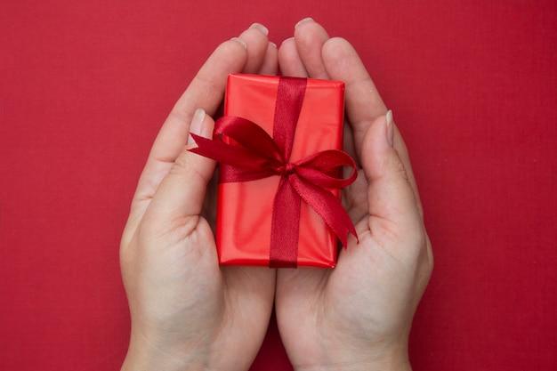 Femininas mãos segurando uma caixa de presente de natal vermelha com fita vermelha e arco, sobre fundo vermelho. Foto Premium