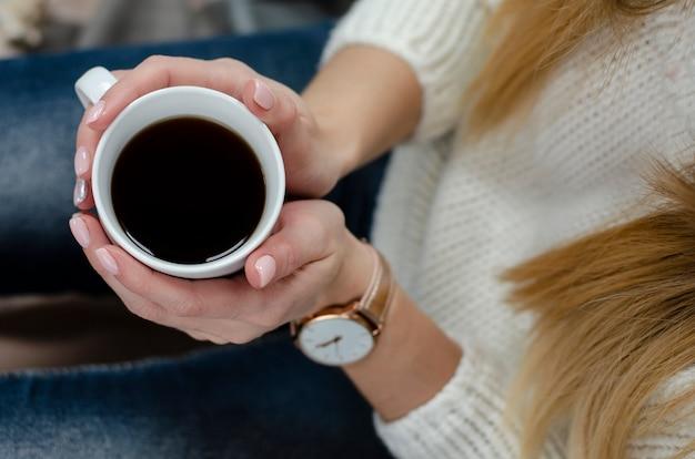 Femininas mãos segurando uma caneca branca com bebida. conceito de estilo de vida. vista do topo. fechar-se Foto Premium