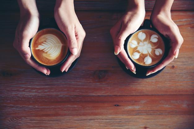 Femininas mãos segurando xícaras de café no fundo da mesa de madeira rústica Foto Premium