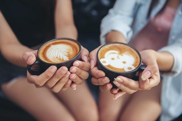 Femininas mãos segurando xícaras de café. Foto Premium