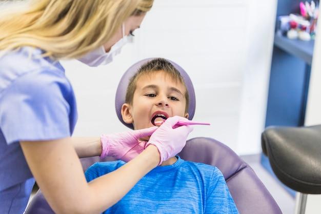 Femininas, odontólogo, verificar, criança, paciente, dentes, com, espelho dental Foto gratuita