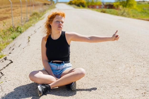 Femininas, sentando, ligado, vazio, estrada, hitchhiking Foto gratuita