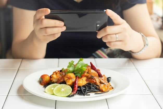 Femininas, tome, foto comida, com, telefone móvel, espaguete, carvão, marisco, ligado, a, tabela, em, restaurante Foto Premium
