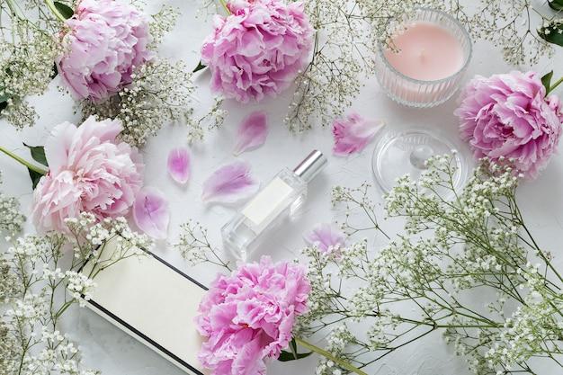 Feminino, blogueiro de beleza, colocar o frasco de perfume, peônias, flores de gypsophila em mármore Foto Premium