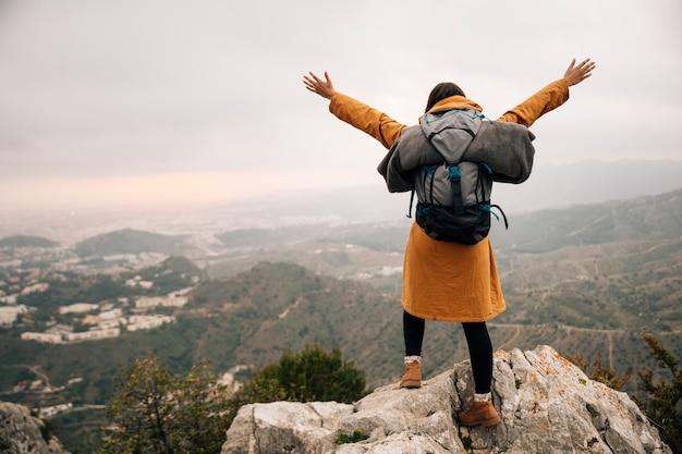 Feminino caminhante com a mochila de braços abertos no pico da montanha Foto gratuita