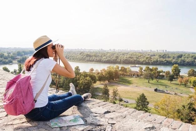 Feminino caminhante olhando a vista através de binóculos Foto gratuita