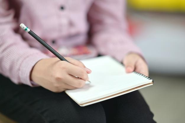 Feminino escrevendo no caderno. Foto Premium