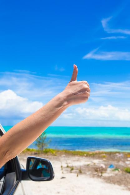 Feminino mão aparecendo polegares na praia Foto Premium