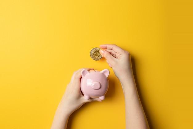 Feminino mão com moeda de bitcoin colocar em um cofrinho Foto Premium