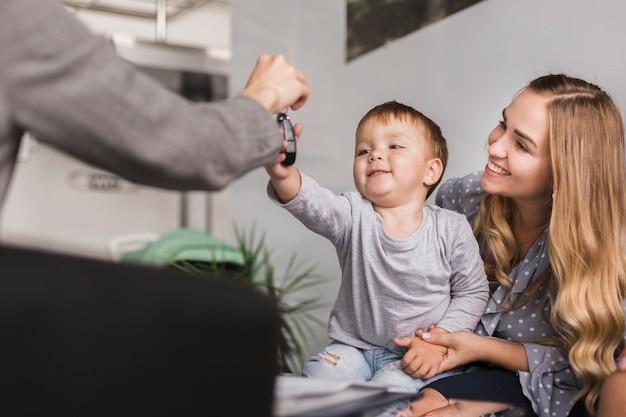 Feminino mão dando as chaves do carro para um bebê Foto gratuita