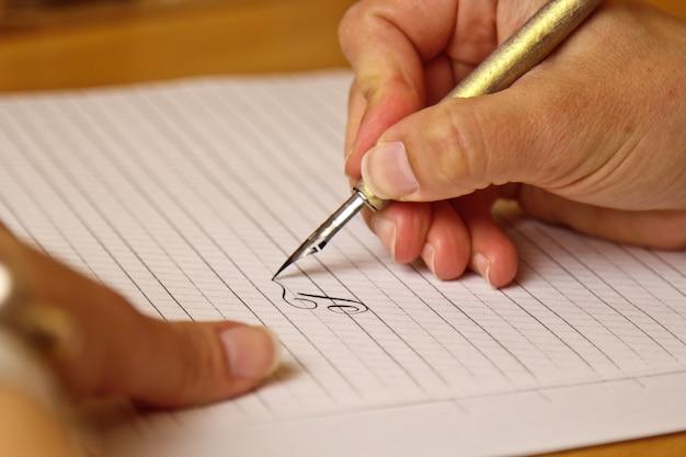 Feminino mão escreve com uma caneta de tinta em uma folha de papel branco com listras. Foto Premium