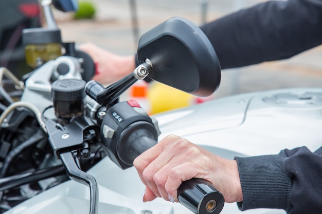 Feminino mão no punho de ajuste de uma velocidade de motociclismo de corrida Foto Premium