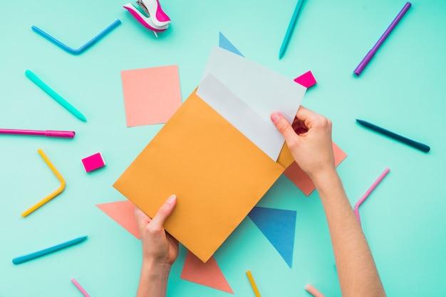 Feminino mão removendo o cartão do envelope sobre os acessórios de papelaria Foto gratuita